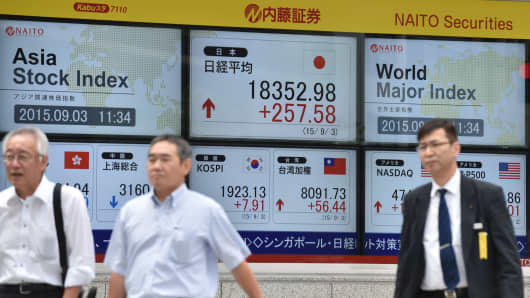 Pedestrians walk past a share price board of the Tokyo Stock Exchange in Tokyo.